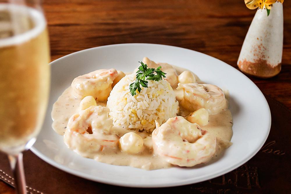 Arroz branco se encontra no centro do prato branco, com camarões flambados com espumante. À esquerda da imagem tem uma taça de espumante