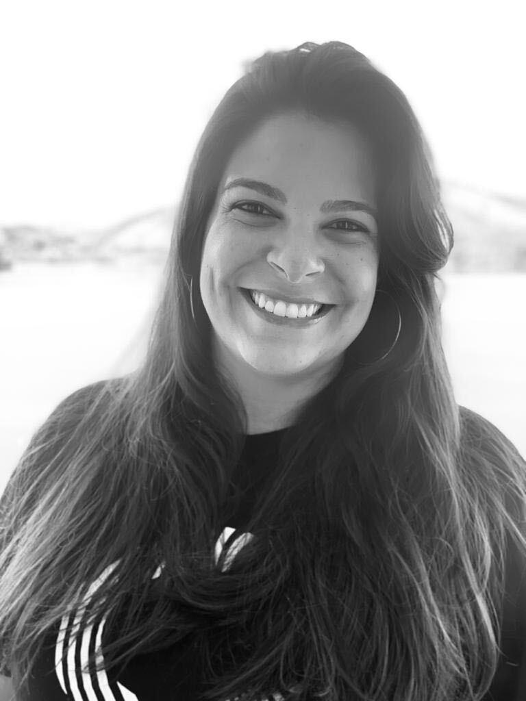Carolina Badaró, COO da startup de mobilidade urbana Quicko, sorri em foto preto e branco.