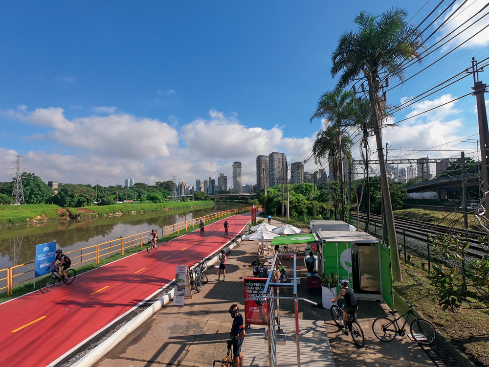 Imagem vista de cima da ciclo faixa do Rio Pinheiros. Há ciclistas de capacete utilizando a pista em um dia com céu azul com apenas nuvens ao fundo