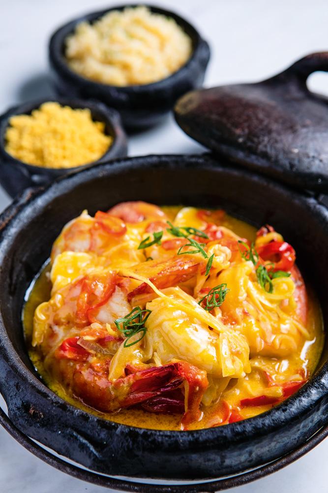 Moqueca de camarão na panela de barro e ao fundo porções de farofa e arroz