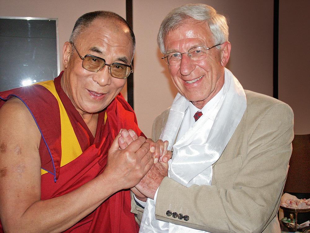 Tenzin Gyatso, o 14º Dalai Lama, com o ativista alemão Franz Alt. Eles posam para a foto de mãos dadas em frente ao peito