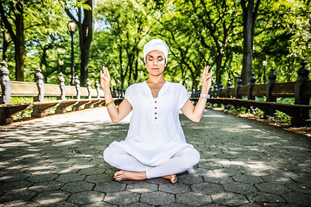 Daniela em pose de meditação, vestida inteira de branco, em um ambiente arborizado e de olhos fechados