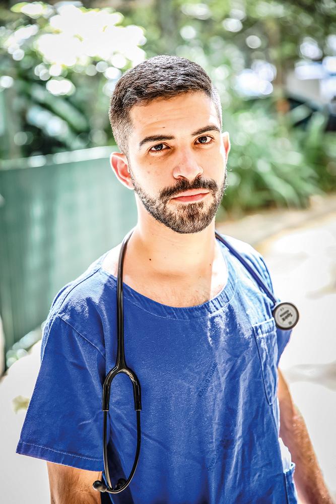 Matheus Gonçalves, com uma roupa azul e um estetoscópio no ombro