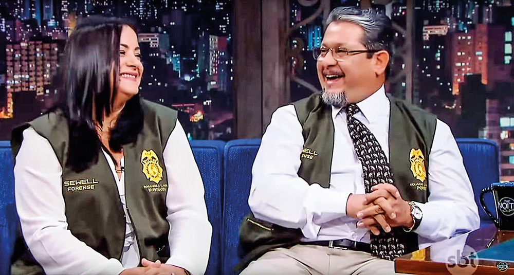 Eduardo e Rosangela sentados em um sofá azul, vestidos com uniforme de criminalistas. Eles estão sorrindo. No fundo há um cenário de um programa de talkshow.