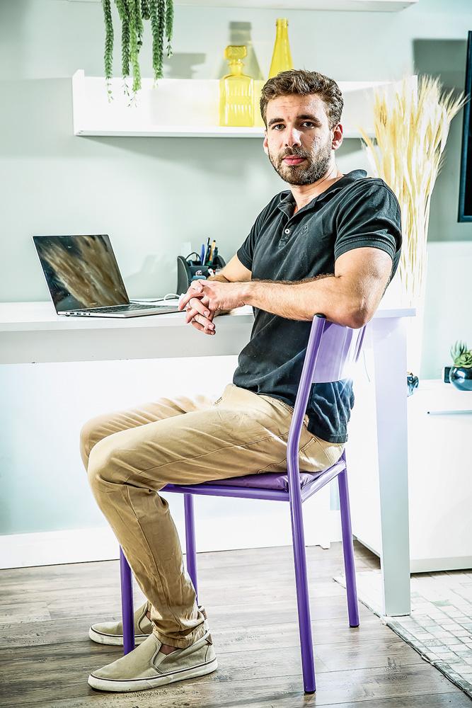 Felipe sentado em uma cadeira, com o braço apoiado sobre o encosto