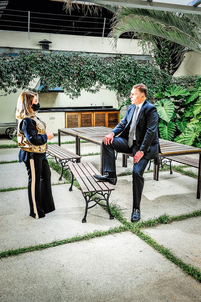Fernando, de lado para a câmera e de frente para Cristina. Ele está com o pé apoiado em um banco.