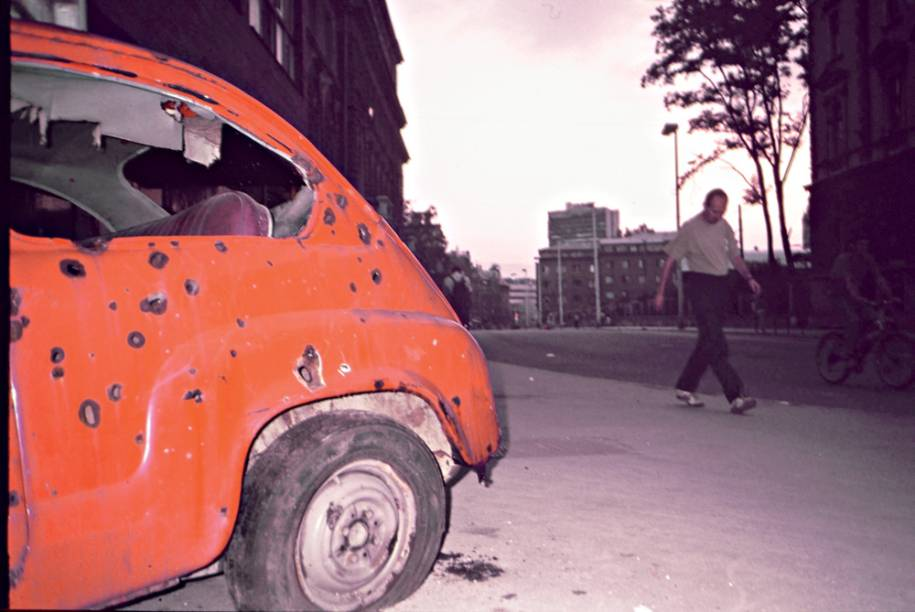 Marcas de bombardeios nas paredes e carro destruído abandonado na rua: cidade-ruína e ecos da violência