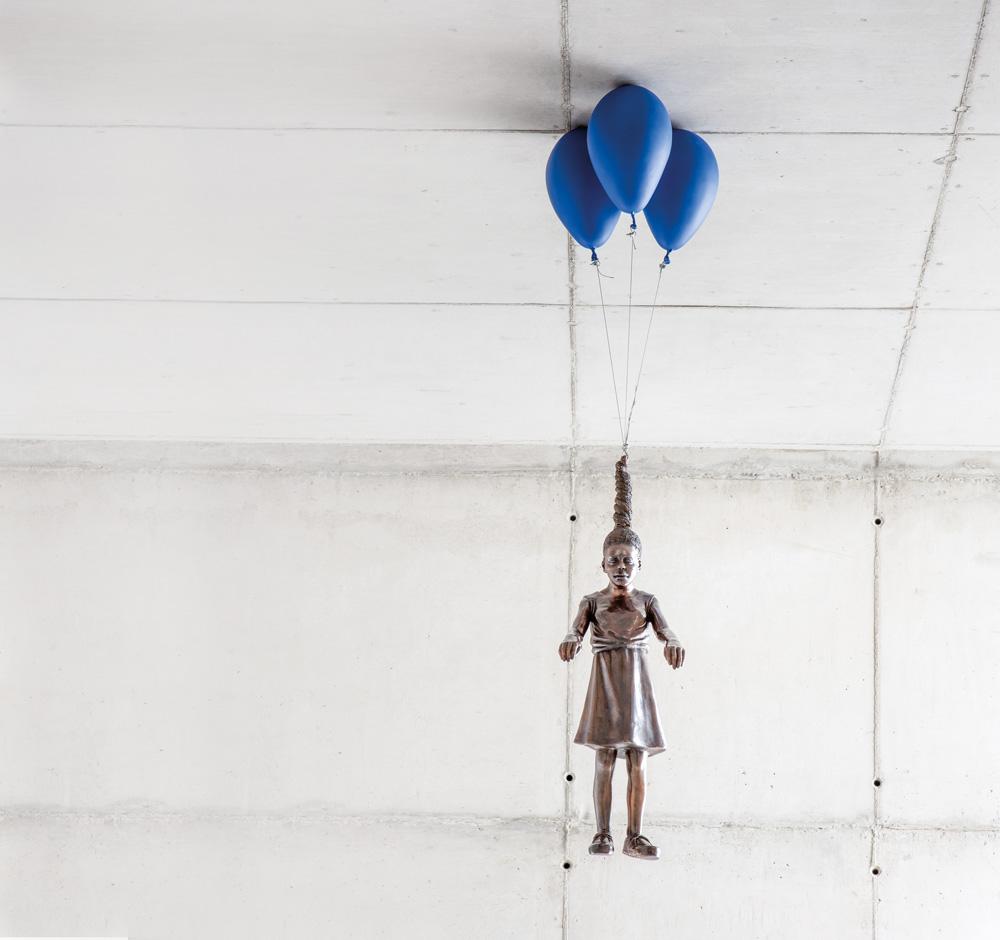 Escultura de Flávio Cerqueira em bronze com uma menina de pendurada no teto da Galeria Leme por três bexigas
