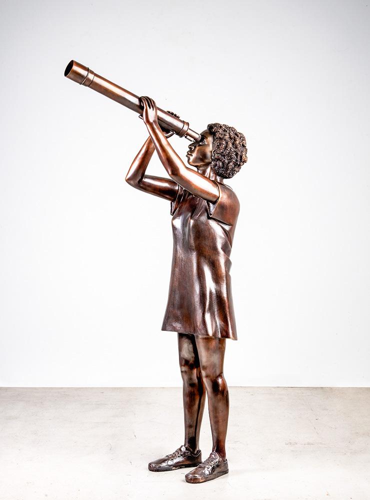Escultura de Flávio Cerqueira em bronze de um menino observando em uma luneta
