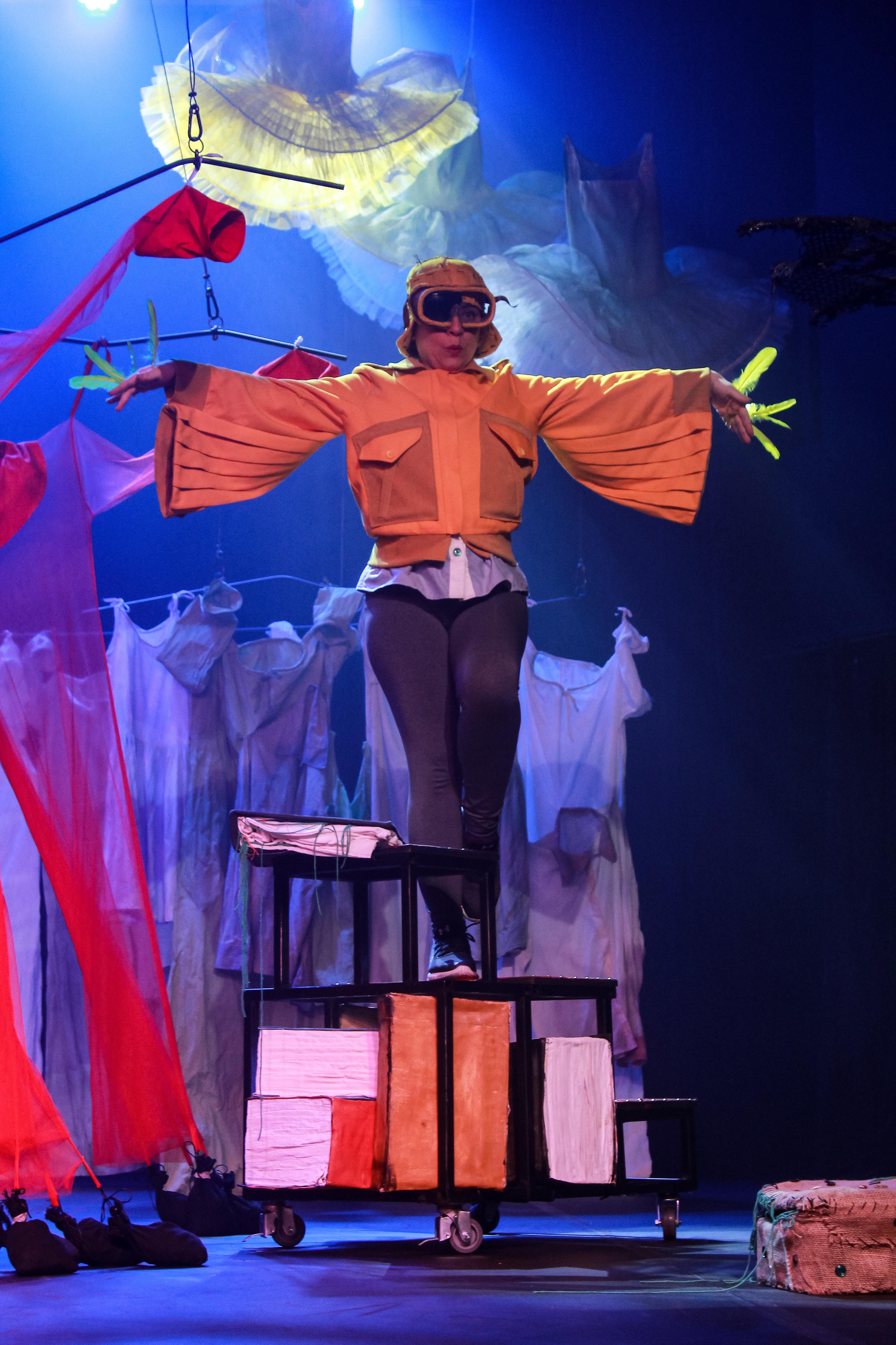 Em palco de teatro, uma mulher fantasiada de pássaro faz pose de voo, em cima de uma superfície com livros