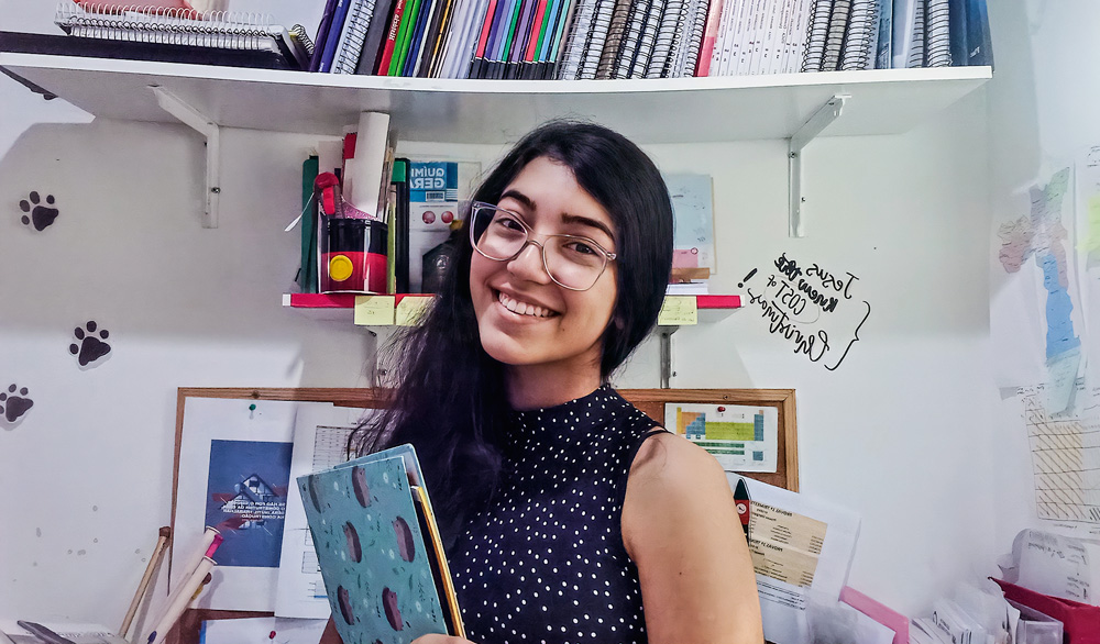 Giovanna posando para foto sorrindo e segurando caderno