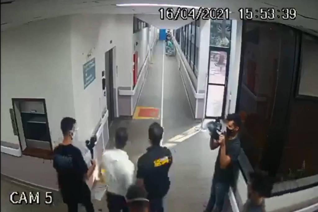 Imagem de câmera de segurança mostra quatro pessoas entrando em hospital.
