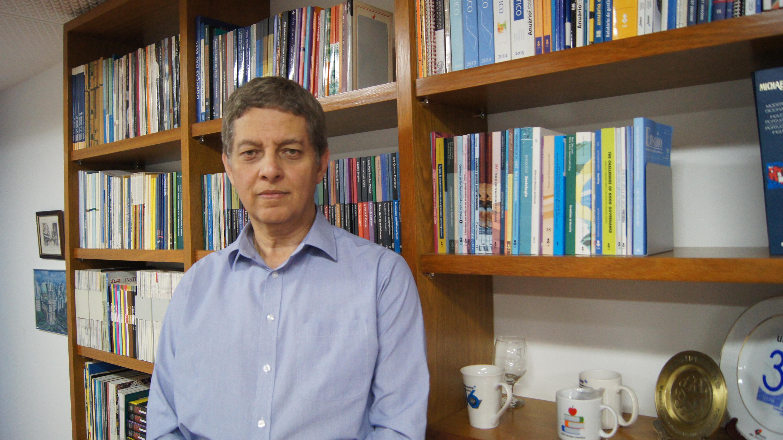 Jézio Gutierre, diretor-presidente da Fundação Editora da Unesp, posa em frente a estante de livros.