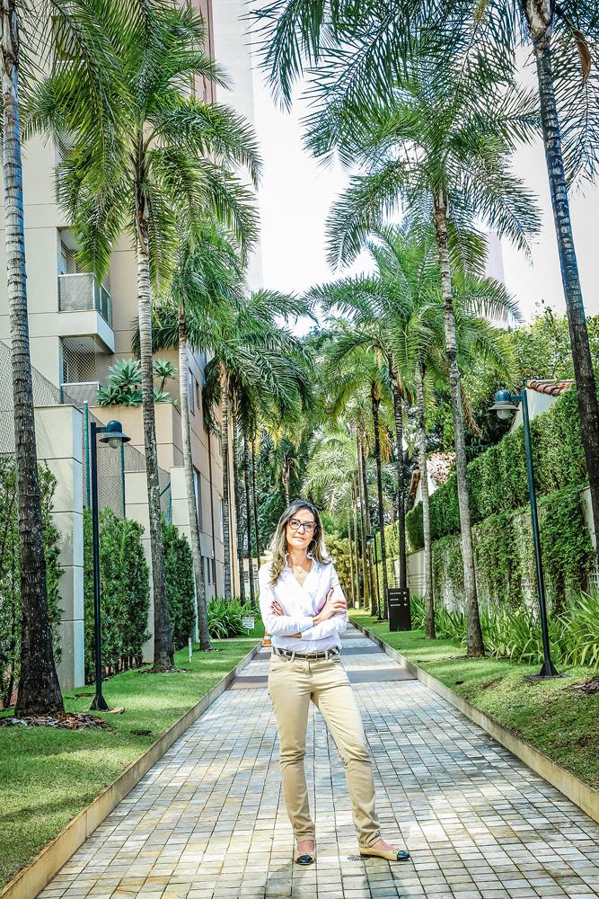 Ligia, em um corredor arborizado em um dos condomínio. Ela está de pé e há palmeiras em volta.