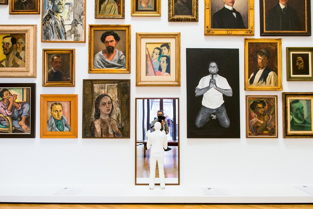 Vários quadros dispostos em uma parede branca, um deles é um espelho e da para ver o fotógrafo tirando a foto