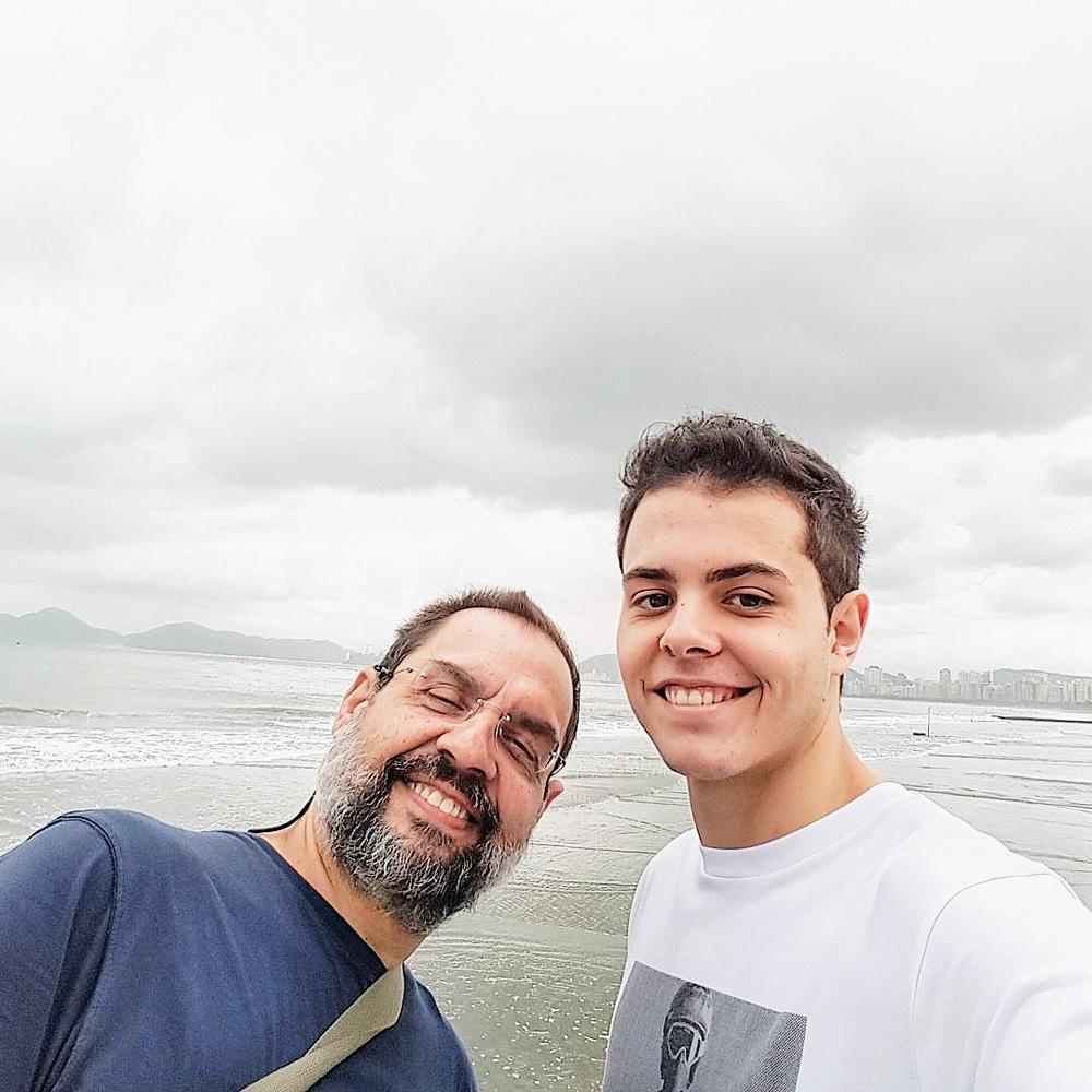 Lucas tira uma selfie com o pai, e na fotografia estão os dois sorrindo com uma praia ao fundo
