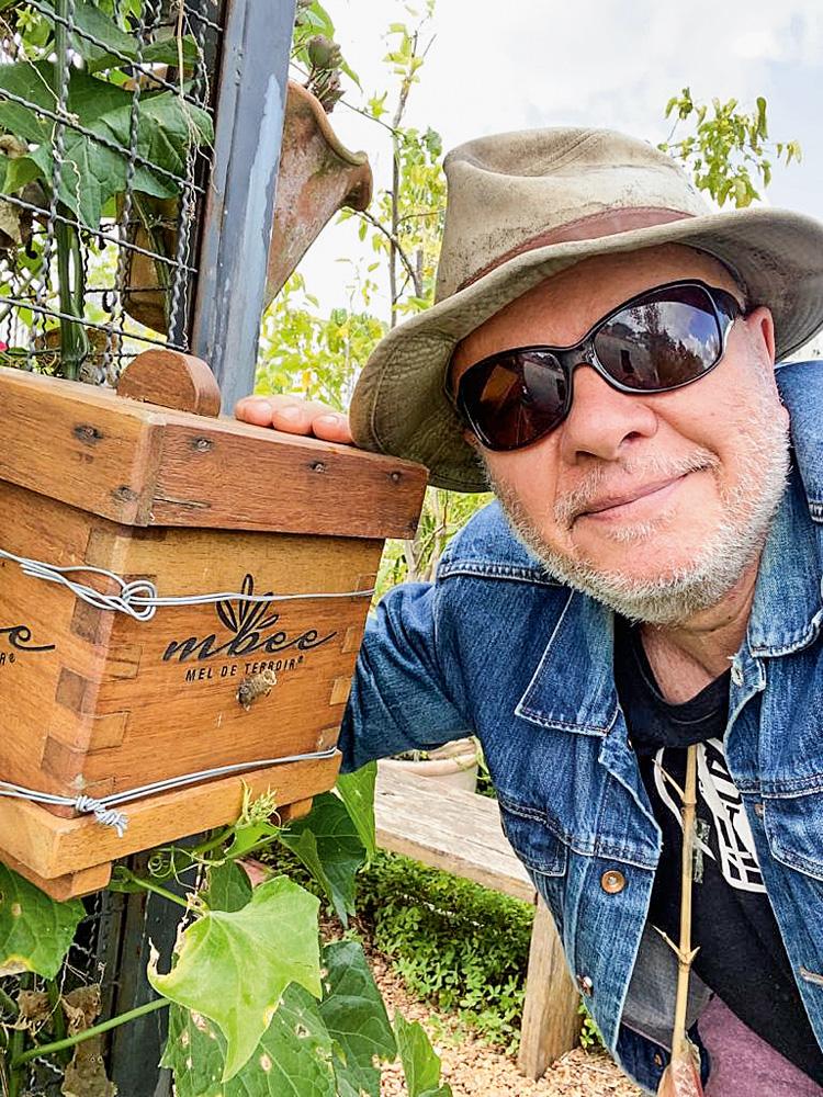 Marcelo Tas, de óculos escuro, com um braço sobre a sua caixa de criação.