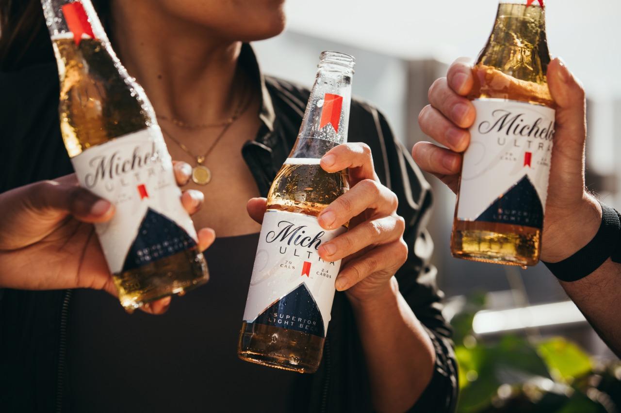 Três pessoas seguram garrafas da cerveja Michelob Ultra, onde o foco da imagem são apenas as mãos e as cervejas