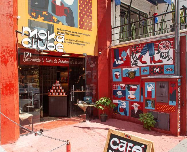 Foto angulada pelo canto esquerdo da fachada da loja Moka Clube. Paredes vermelhas cobertas por pôsteres azul e branco do lado direito e porta de vidro do centro para a esquerda.