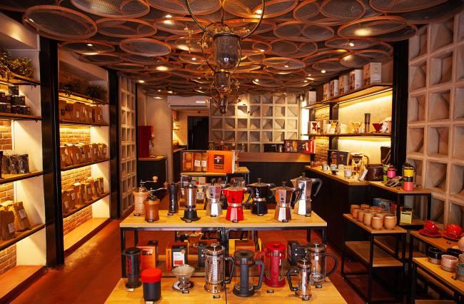 Loja de café com prateleiras de madeira à esquerda e à direita cobertas por sacos pardos de café e xícaras de cerâmica. Ao centro, estante de madeira e estrutura metálica preta com cafeteiras italianas, moedores manuais de café e prensas francesas.