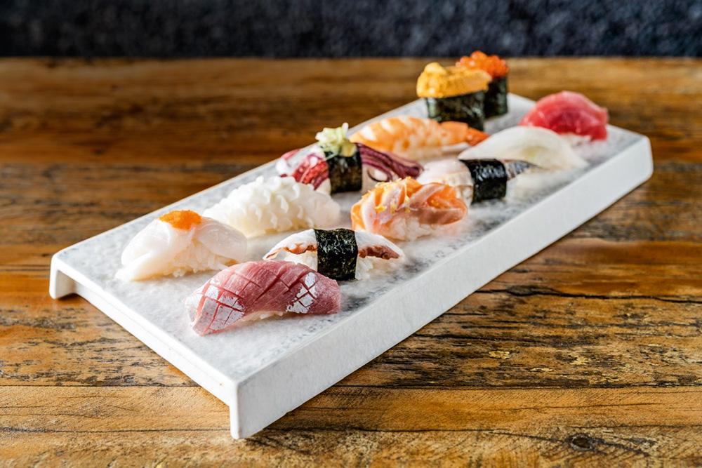 Onze sushis em duas fileiras numa bandeja retangular branca que está em cima de um bancada de madeira.