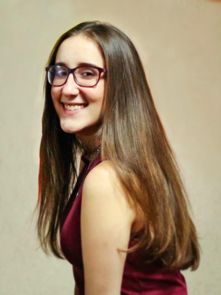 Natalia sorrindo para a foto com corpo de perfil