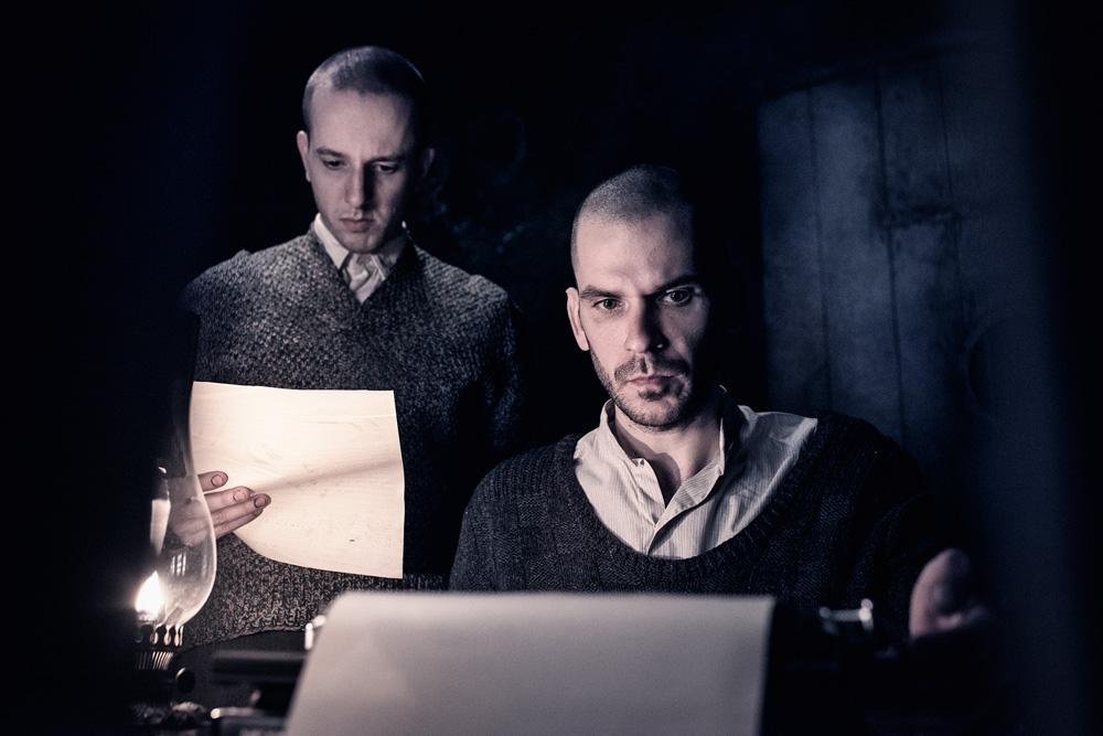 Os dois eslovacos, em uma foto escura. Um deles está em pé com uma folha em mãos e o outro está escrevendo numa máquina de escrever