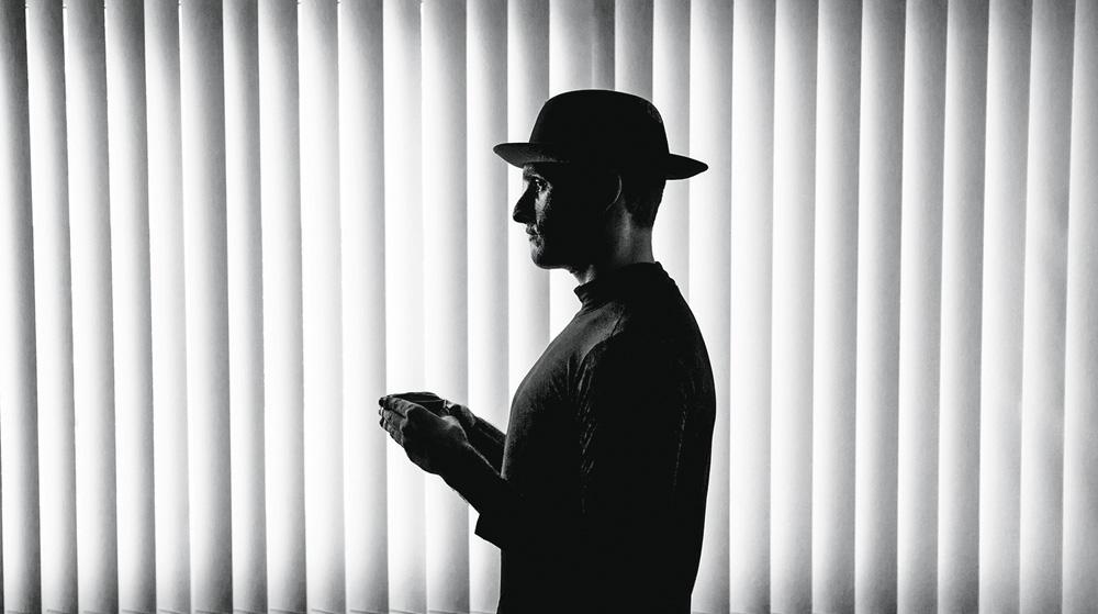 Homem de perfil com as mãos em frente ao peito. Foto escura e preta e branca