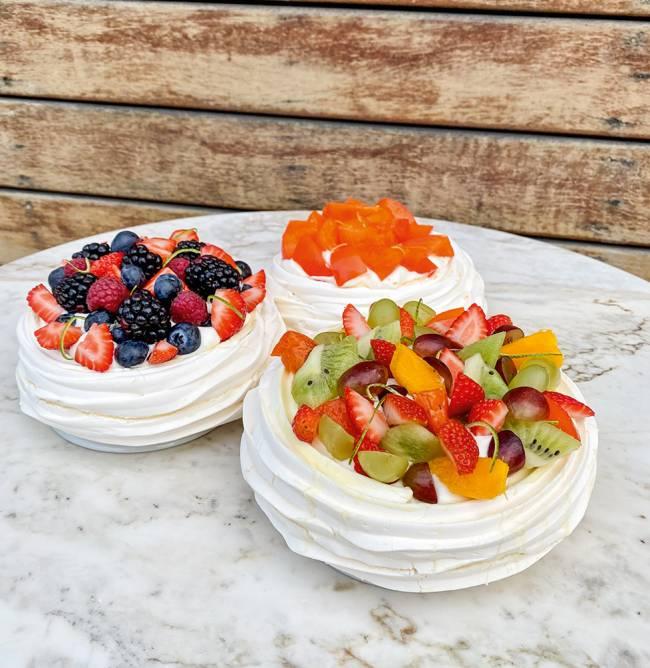 Três pavlovas postadas em cima de uma mesa de granito, uma coberta de mix de frutas, outra de frutas vermelhas e a última, mais ao fundo, de caqui.