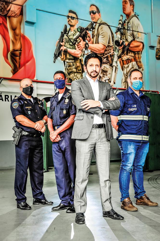 Vice-prefeito Ricardo Nunes e membros municipais do Comitê de Blitze, todos exceto Ricardo de máscara, em pé, posando para a foto com olhar sério
