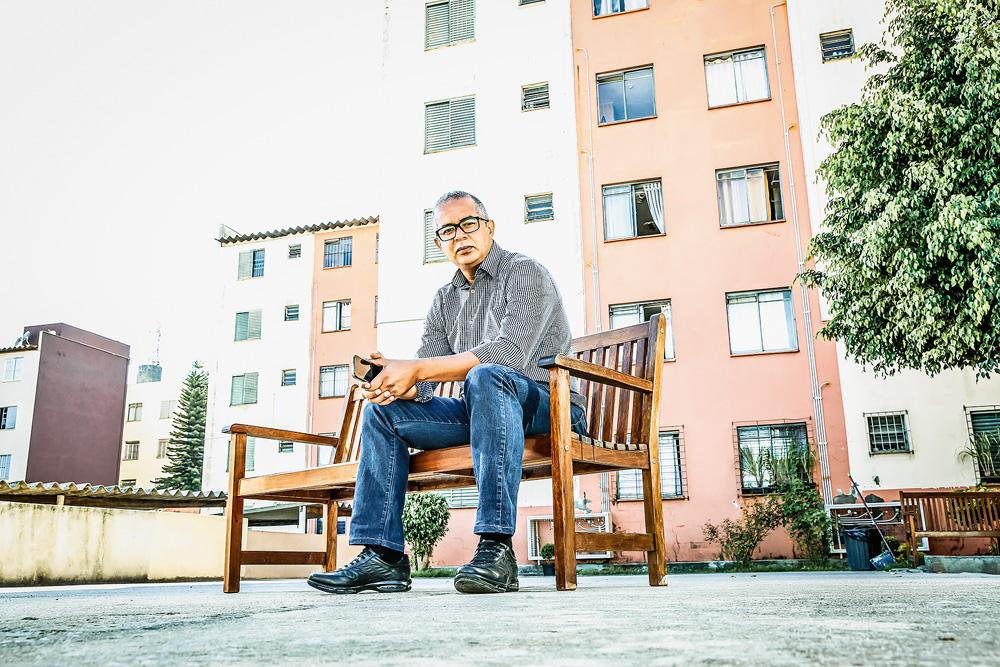 Rodrigo olhando para câmera, que está observando de baixo. Ele está sentado em um banco de madeira.
