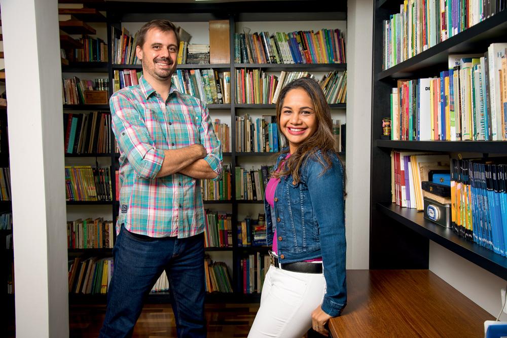 O casalGuilherme Trivellato, 37, e Katherine Giron Perez, 42, posam em frente a estantes de livros