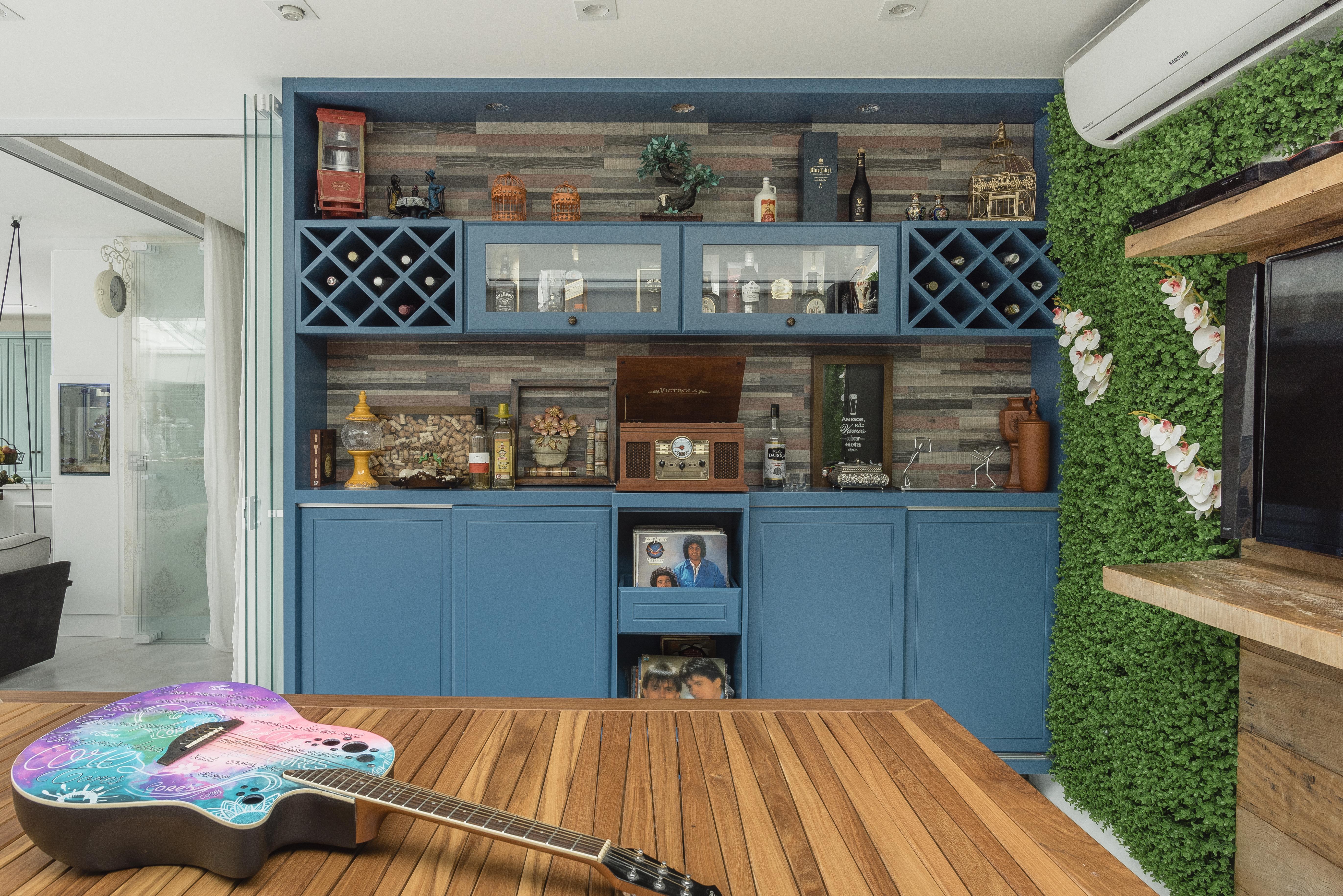 Móveis na cor azul e mesa de madeira de demolição ocupam espaço da casa reformada do músico Marcos. Na mesa, aparece uma guitarra colorida.