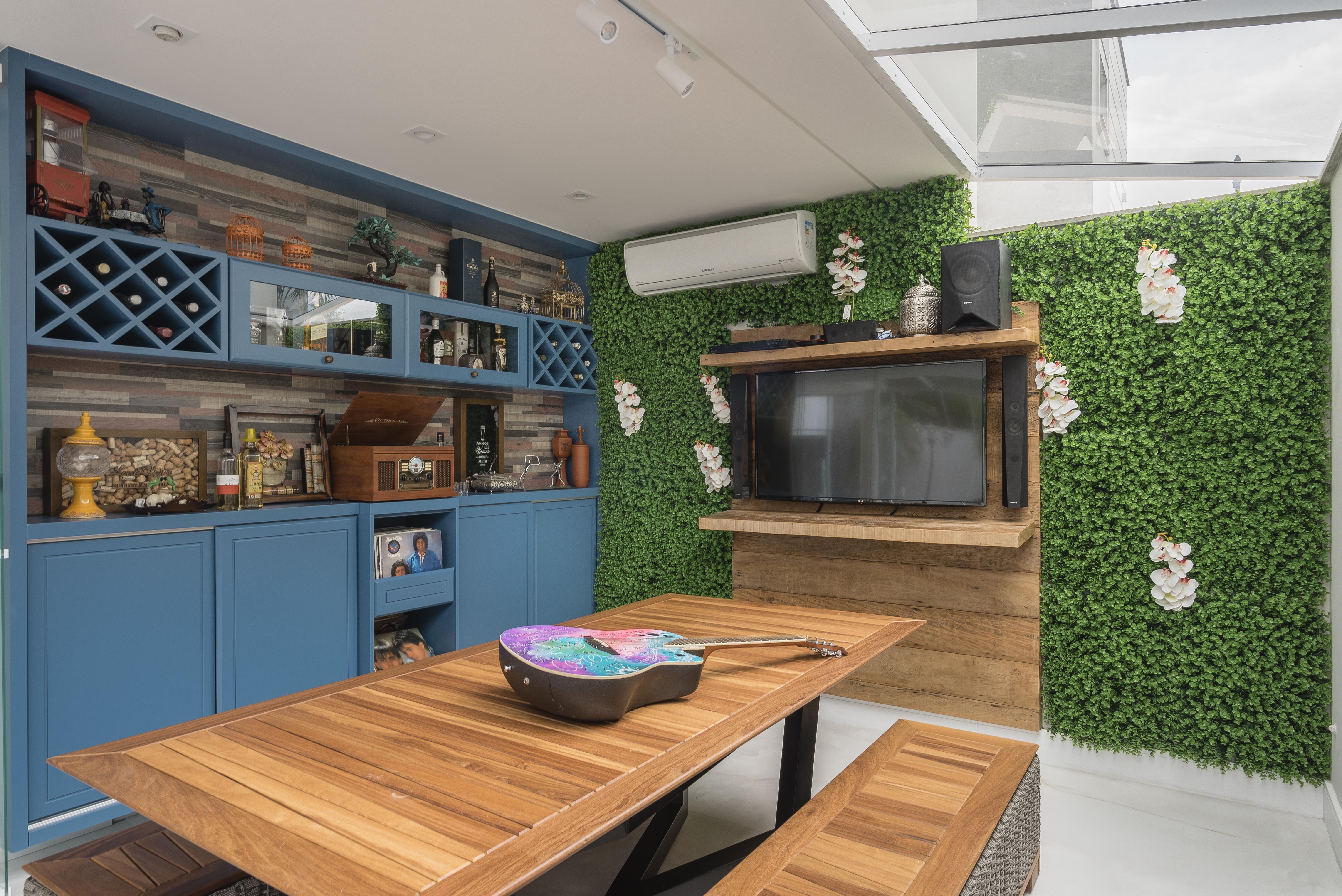 Móvel azul, parede com grama sintética e mesa de madeira aparecem na foto. Em cima da mesa, uma guitarra colorida.
