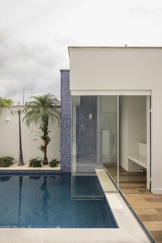 Parte da piscina da casa do músico Marcos, de Marcos & Belutti. Ao fundo, plantas e muro branco aparecem na foto.