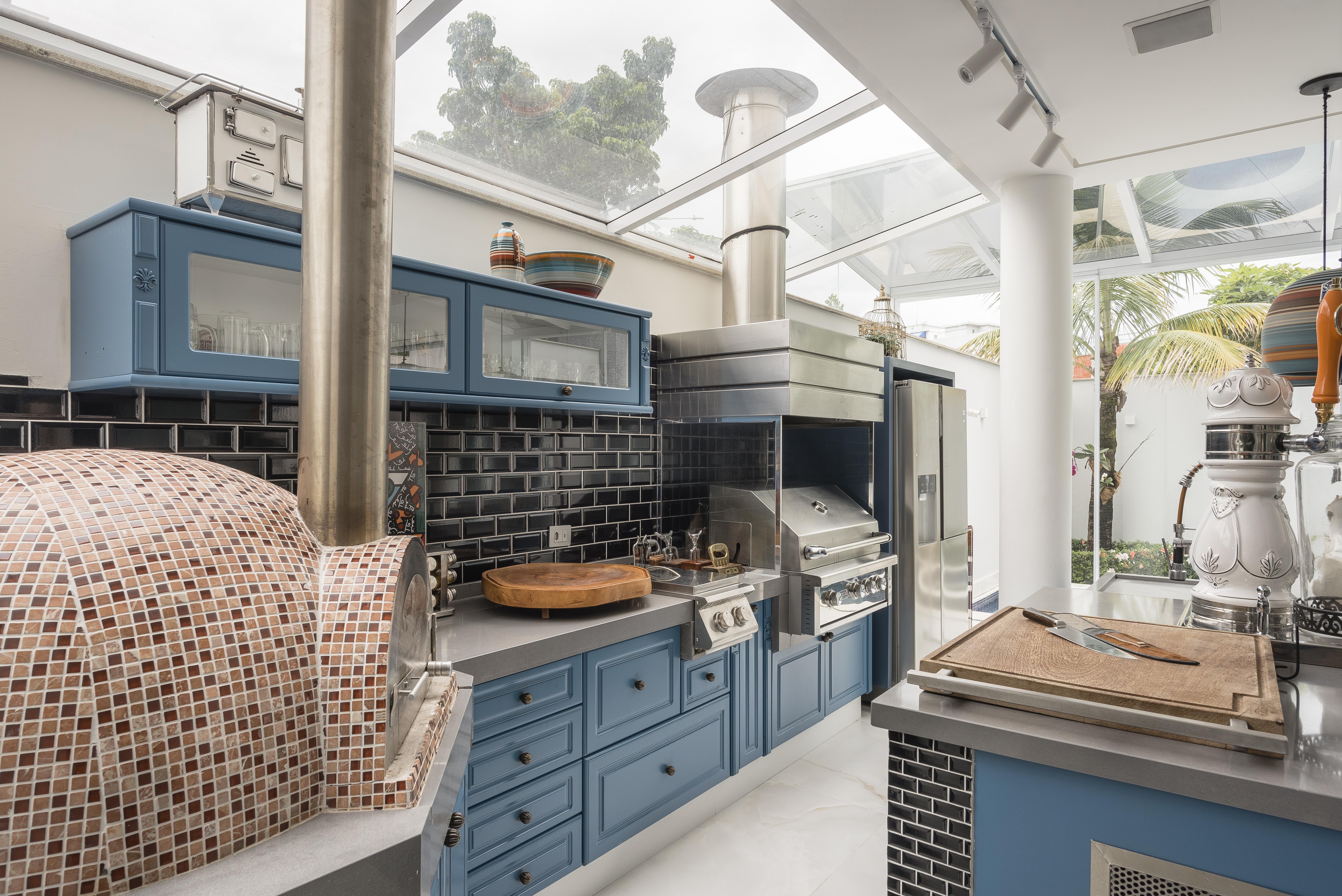 Cozinha com móveis azuis e forno com ladrilhos aparecem na imagem.