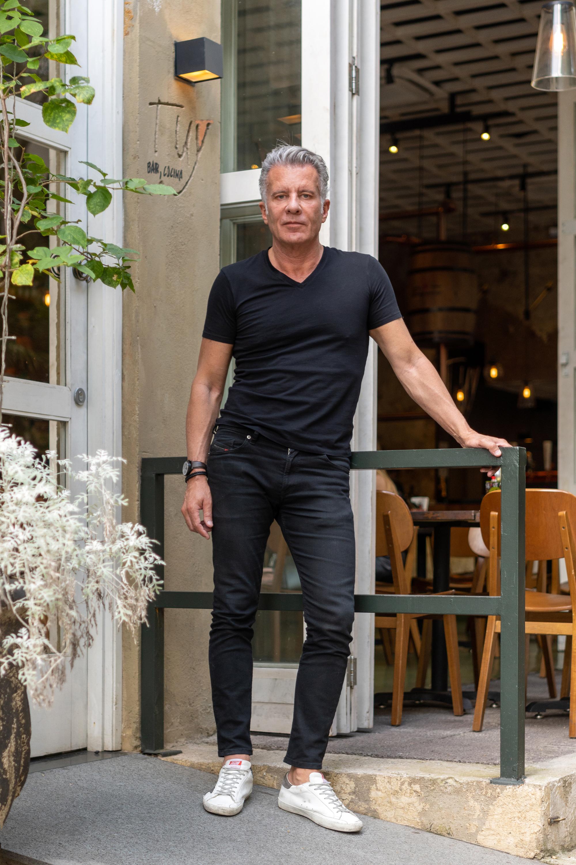 Homem de pé usando roupas pretas e com o braço esquerdo apoiado em uma barrra de ferro