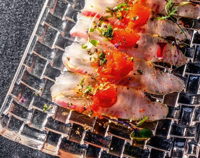 Prato retangular transparente com fatias de peixe finas cobertas por ovas de peixe e pimenta.
