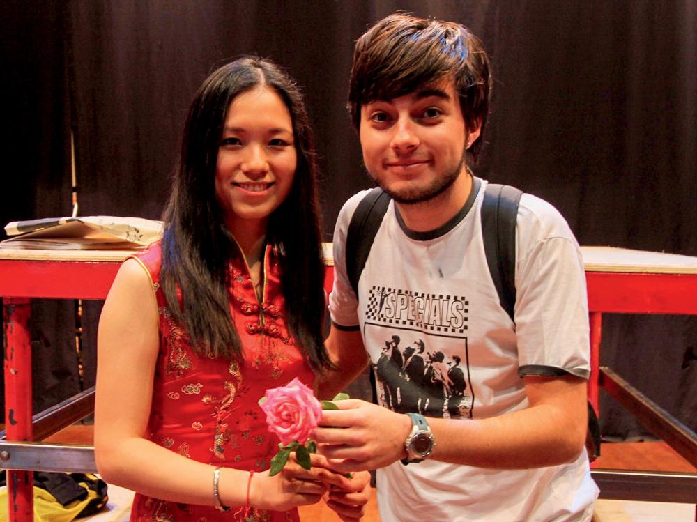 Sisi e Lucas estão próximos um do outro posando para a foto. Sisi segura uma flor