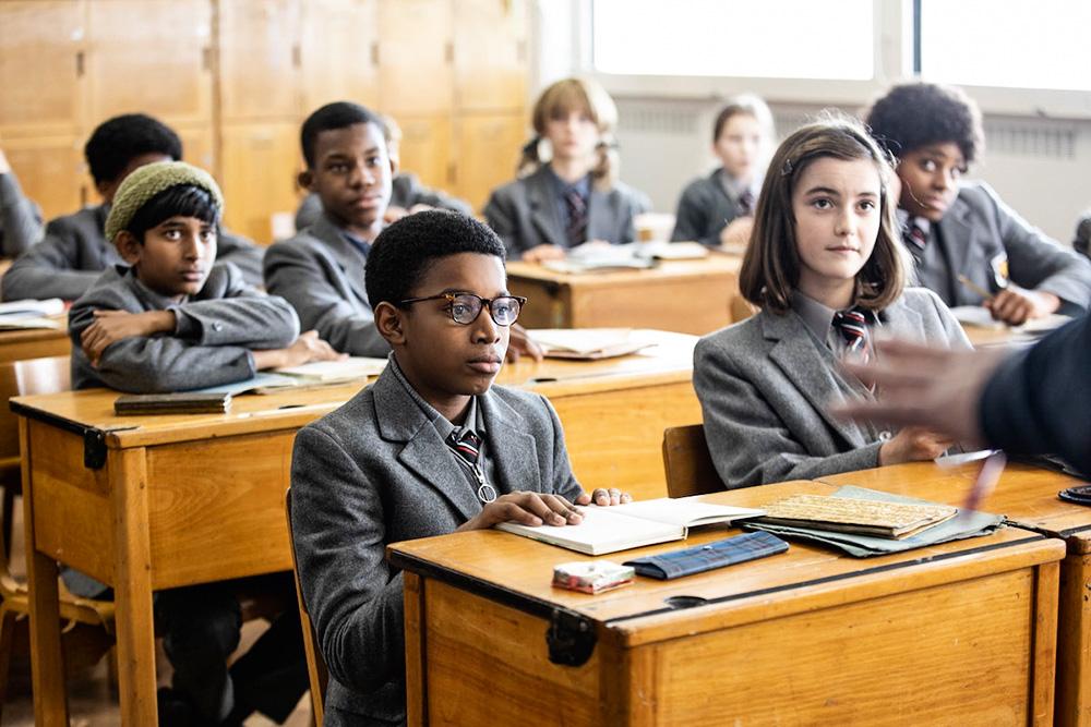O personagem Kingsley no centro de imagem, dentro de uma sala de aula com outros colegas. Todos estão sentados e olhando para frente