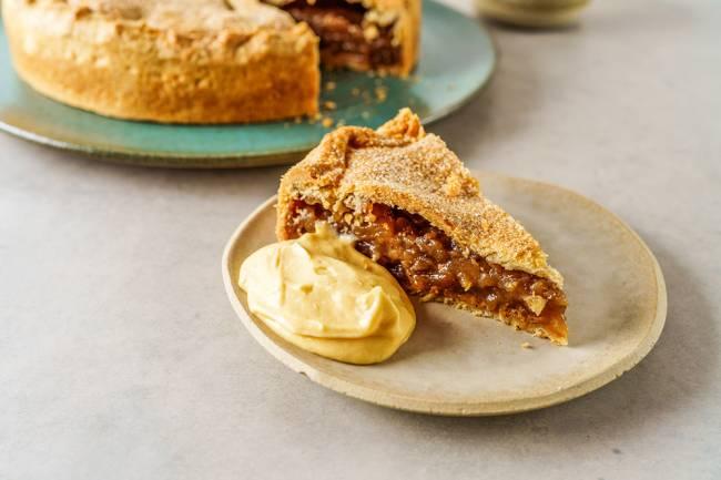 Pedaço de torta de maçã sobre prato de cerâmica ao lado de creme amarelado. Ao fundo, a torta inteira sem o pedaço à frente.