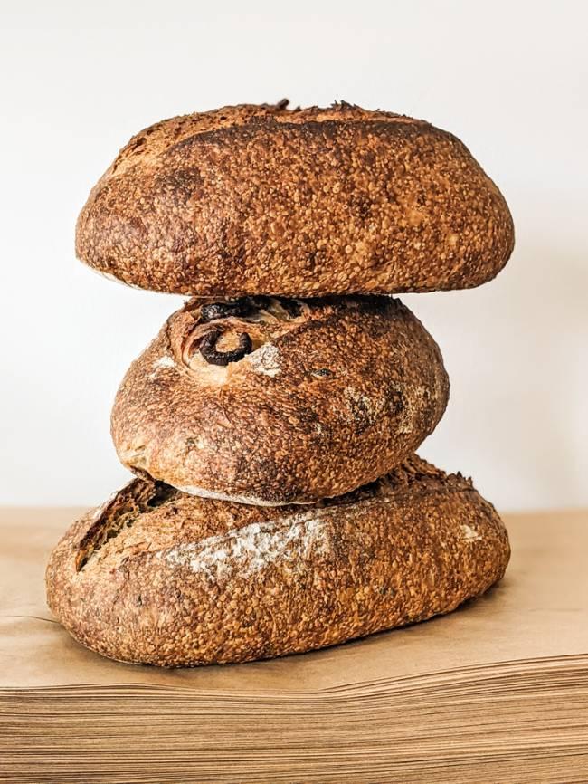 três pães assados., da cassa, de azeitonas e de grãos, empilhados