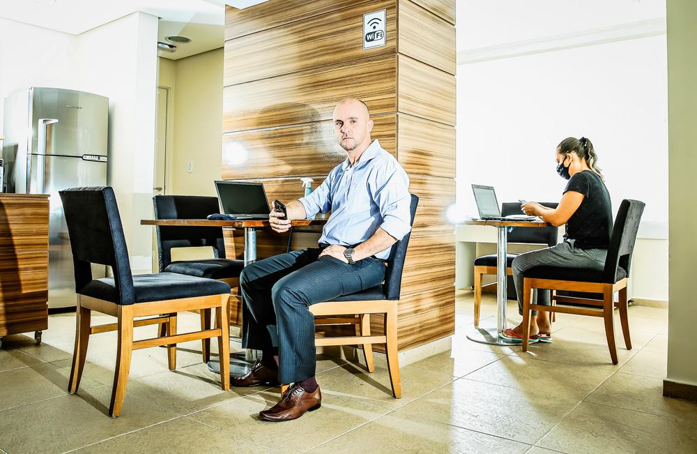 Vagner sentando em uma cadeira, com o braço apoiado numa mesa e há também um notebook desligado.