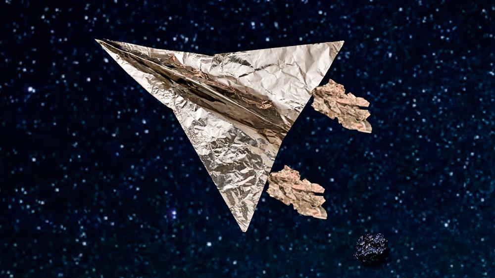 Nave espacial feita com papel alumínio em fundo feito digitalmente sobrevoa por estrelas