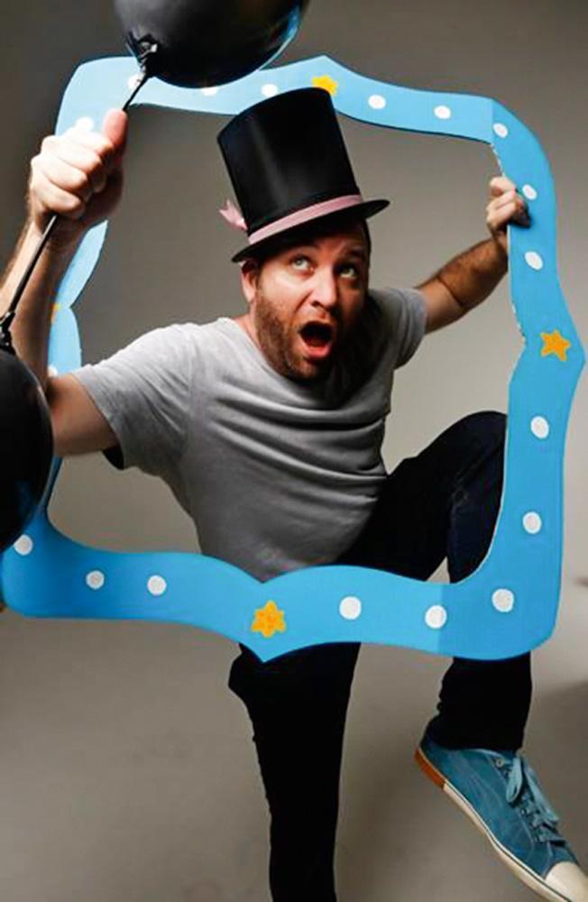 Ioram Finguerman segura uma moldura em papel de quadro e faz uma pose olhando para cima, enquato usa um chapéu na cabeça