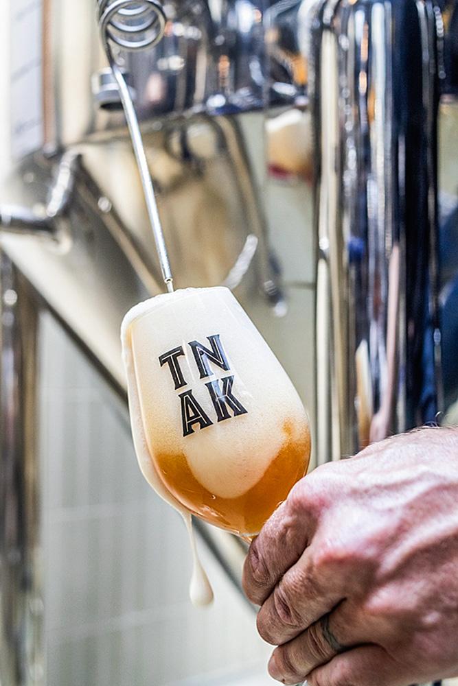 Pessoa se servindo da cerveja direto do barril. Na imagem aparece uma mão da cor branca, com a taça de vidro com o logo do tank, enquanto a cerveja sai do barril.