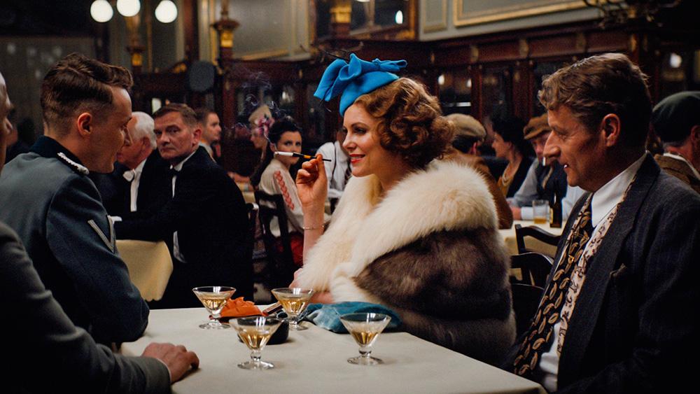 Cena do filme A Espiã, em que a protagonista está em uma mesa de um restaurante com outros homens