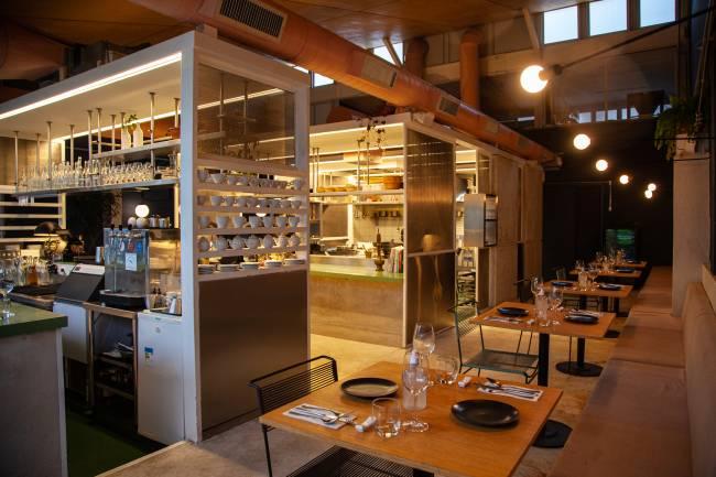 restaurante com mesas postas à direita e cozinha aberta por janela de vidro ao fundo à esquerda