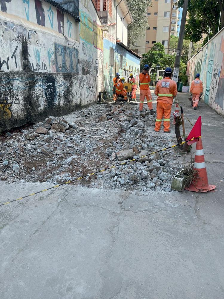 Funcionários da prefeitura reparando asfalto da travessa