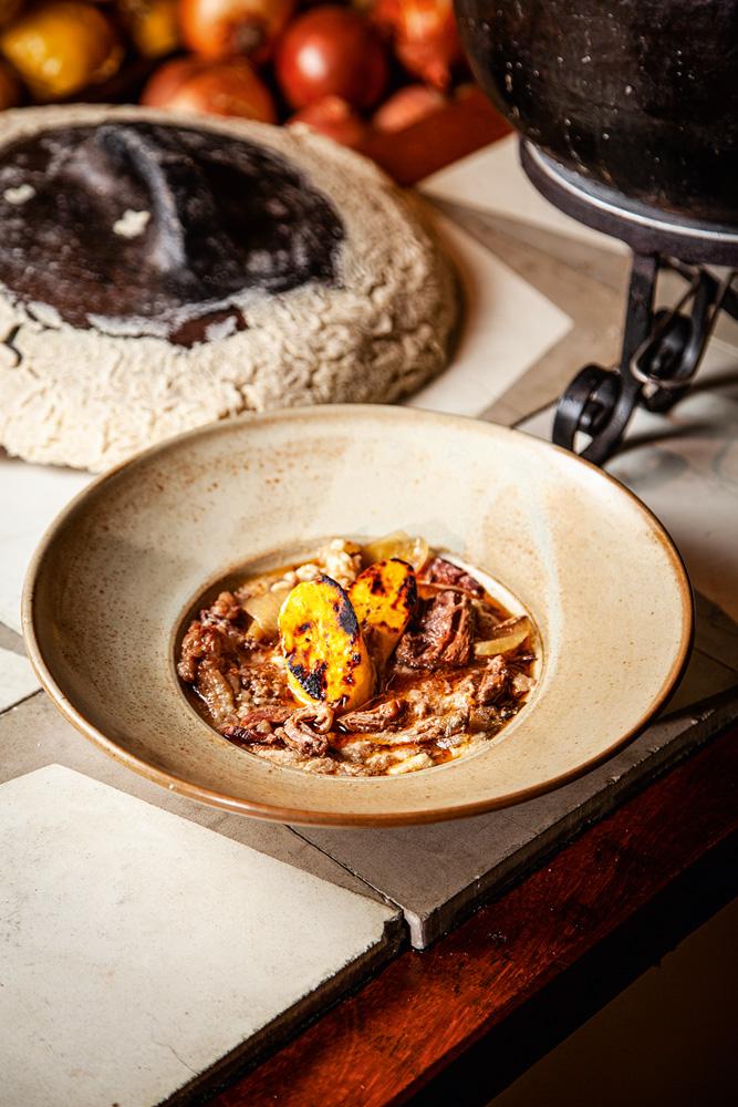 Prato com cozido de carne bovina junto de banana-da-terra grelhada e farinha de mandioca